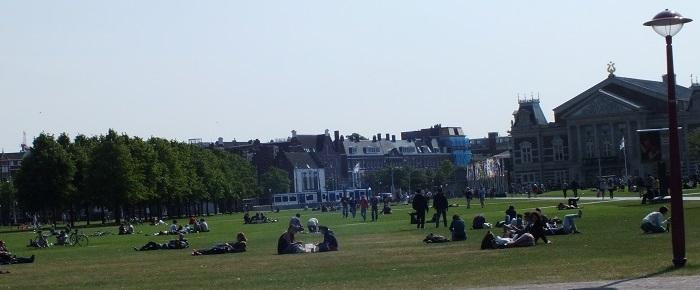 vista panorámica de un parque en Amsterdam con gente sentada o tumbada sobre el césped con poca sombra, bicicletas,gente pasando o tomando el sol